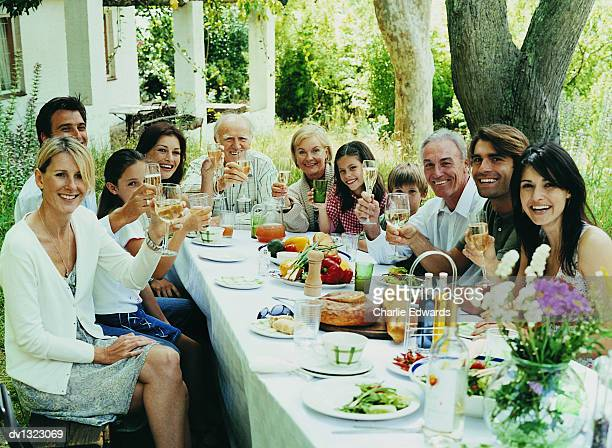Large Portrait of a Family Sitting at a Table Outdoors in a Lush Garden