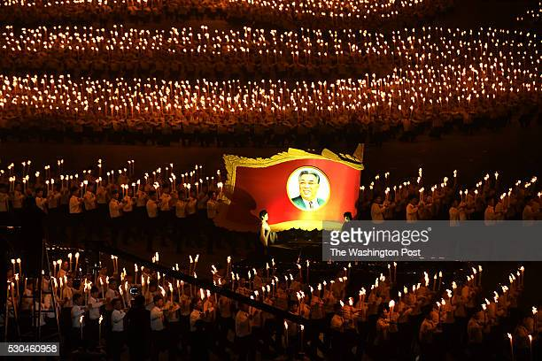 A large portrait of Kim Il Sung the Eternal President is surrounded by thousands in a torch parade in Kim Il Sung Square in Pyongyang North Korea on...