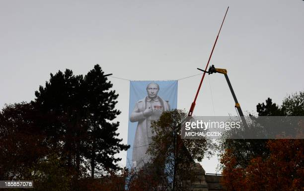 A large poster featuring Russian President Vladimir Putin in a trademark gesture of Soviet dictator Joseph Stalin is displayed in front of the...