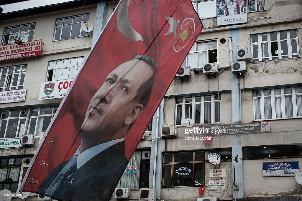 A large poster of Turkish president Recep Tayyip Erdogan is seen hanging over a main street on October 25, 2016 in Rize Turkey. Although born in Kasimpasa, Istanbul, President Erdogan's family was originally from Rize a conservative town on the Black Sea. His family returned to Rize when Erdogan was very young staying until he was 13, before returning to Istanbul. Since the failed coup attempt on July 15, 2016 which saw 240 people killed including 173 civilians, Turkish authorities initiated a state of emergency, leading to an unprecedented crackdown on individuals and organizations with links to US-based cleric Fethullah Gulen and his organization blamed for instigating the uprising. The purge, targeting teachers, journalists, soldiers, judges, academics, police, military leaders, schools and universities has so far seen approximately 100,000 people dismissed, 70,000 detained, 32,000 arrested, 130 media outlets closed and some 15 universities shuttered. The failed coup and subsequent purge only appears to have further bolstered the president's popularity and increased nationalism across the country with July 15th having been marked as a new national holiday. Turkish flags, already prominently displaying all over have increased in numbers, as well as posters of those killed fighting the coup plotters appearing in train stations and public squares. The Bosphorus Bridge in Istanbul, which saw heavy fighting during the coup has been renamed the '15th July Martyr's Bridge'. These changes, follow a year of instability in the country with constant terrorist attacks, an economic downturn, plummeting tourism, and a refugee crisis, all contributing to Turkish society undergoing its most dramatic restructuring in decades.