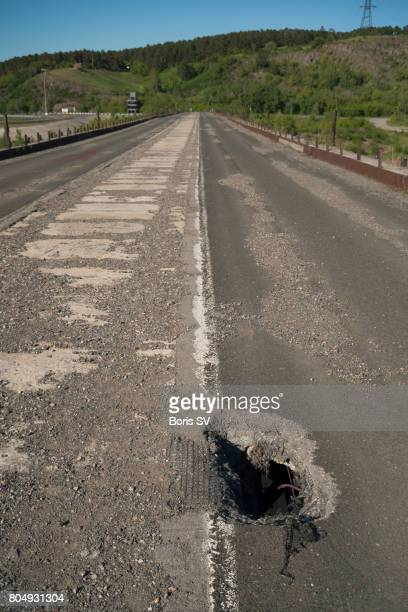 large pothole on the decommissioned bridge in kemerovo, siberia - pothole stock photos and pictures