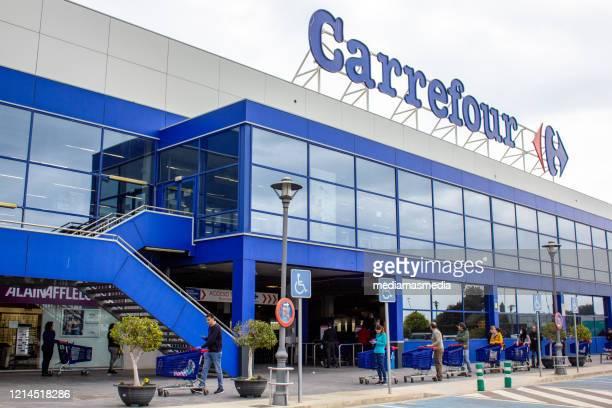 une grande file d'attente de clients attendant d'entrer dans le supermarché pour faire leurs achats durind la pandémie de coronavirus à valence, espagne - carrefour photos et images de collection
