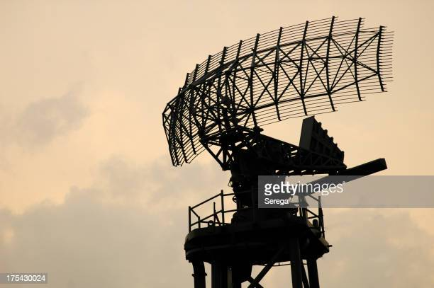 Large radar antenna against a cloudy sky