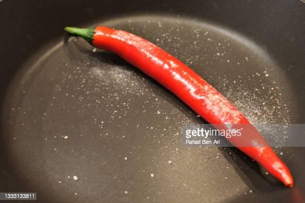 large red chili in a frying pan - rafael ben ari fotografías e imágenes de stock