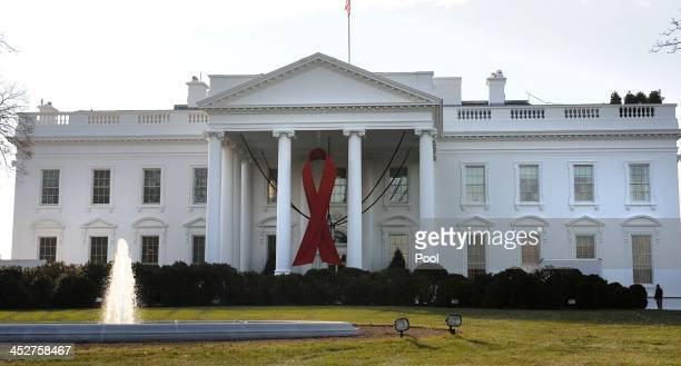 A large red ribbon hangs on the North Portico of the White House for World AIDS Day December 1 2013 in Washington DC Activists advocates and people...