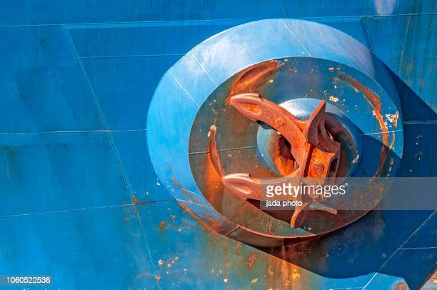 large rusty anchor hangs on the blue ship - rust colored stock photos and pictures