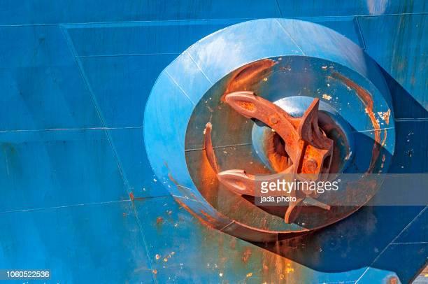 large rusty anchor hangs on the blue ship - rust colored fotografías e imágenes de stock
