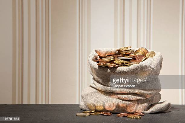 large sack full of euro coins on a table - money bag stock pictures, royalty-free photos & images