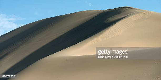 A Large Sand Dune Against A Blue Sky With Shadows Cast On One Side