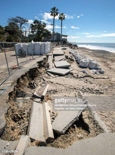 Large sandbags sit in the parking lot next to where the sidewalk and part of the parking lot have collapsed and been washed away at Capistrano Beach...