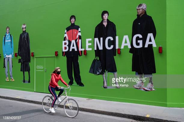 Large scale action figures wearing fashionable clothing against a huge green hoarding which covers the Balenciaga store during a refit in the...