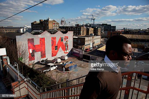 Large scale letters covering a promotional mural spell out 'H W' standing for 'Hackney Wick' Street art in the East End of London is an ever changing...
