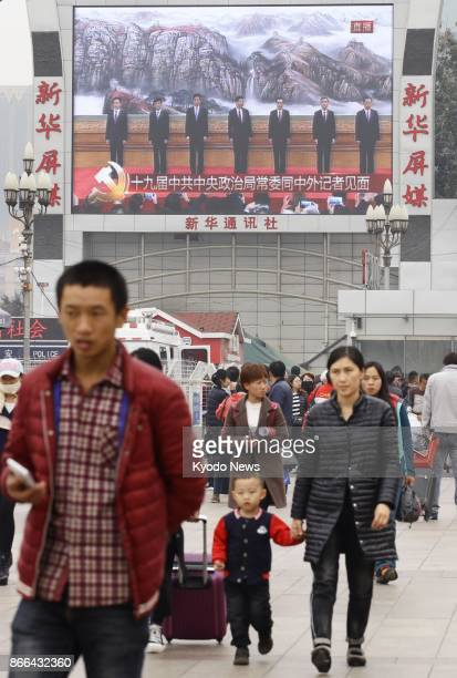 A large screen in Beijing broadcasts a press conference by President Xi Jinping where he unveiled his new leadership team on Oct 25 a day after the...