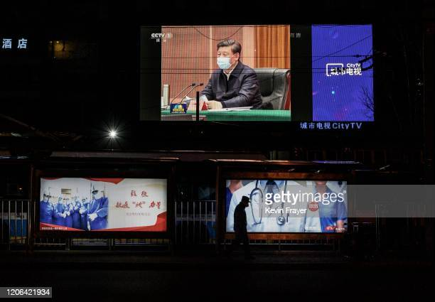 A large screen in the street shows Chinese president Xi Jinping wearing a protective mask during his visit to Wuhan earlier in the day the epicentre...