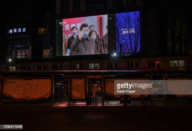 Large screen in the street shows Chinese president Xi Jinping wearing a protective mask during his visit to Wuhan earlier in the day, the epicentre...