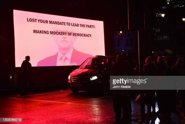 A large screen on the side of a bus shows Jeremy Corbyn with the words Making Mockery Of Democracy during the Leave Means Leave Brexit day...