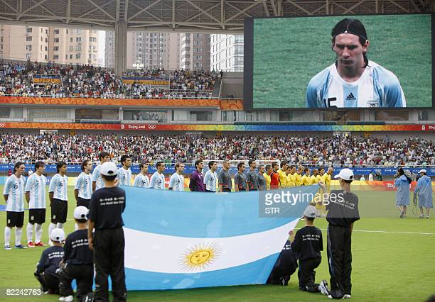A large screen shows Argentina's player Lionel Messi as players of Argentina and Australia listen to the national anthems before their 2008 Beijing...