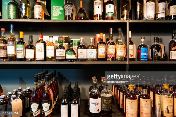 Large selection of bottles of rum and whisky in a row at Borough Market, London, UK