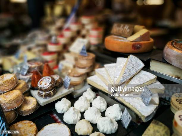 Large selection of camembert cheese, brie and other cheeses on display at Borough Market, London, UK