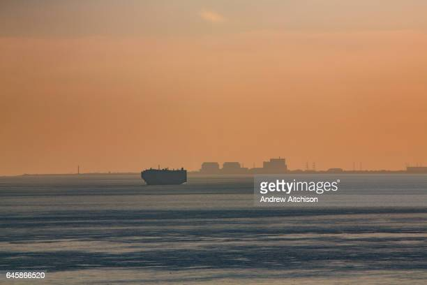 A large shipping container boat anchored in Hythe bay due to bad weather in The English Channel at sunset with Dungeness Nuclear Power Station in the...