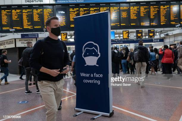 Large sign stands on the concourse of Victoria railway mainline station urges passengers and commuters to wear a face covering while travelling on...