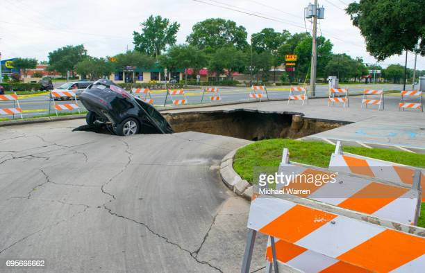 large sinkhole swallows a car in florida - sinkhole stock photos and pictures