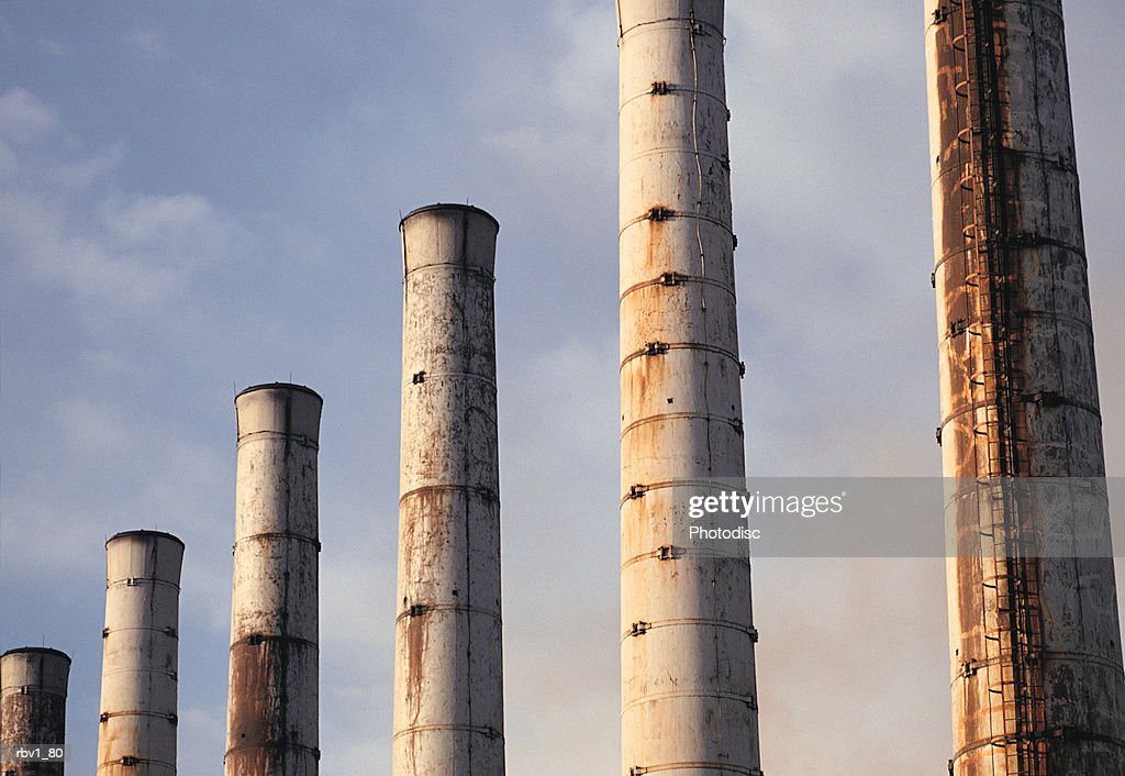 large smoke stacks rise to a blue sky and white clouds : Foto de stock