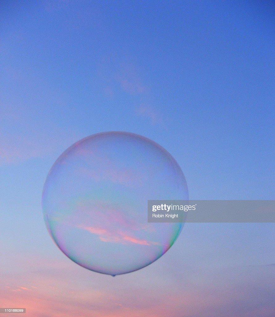 Large soap bubble floats across a pink tinged sky : Stock Photo