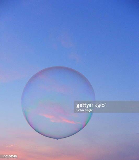 Large soap bubble floats across a pink tinged sky