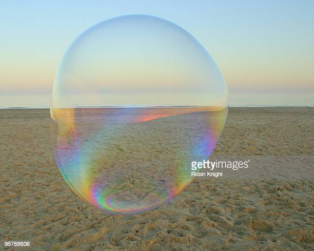 A large soap bubble floats on the beach