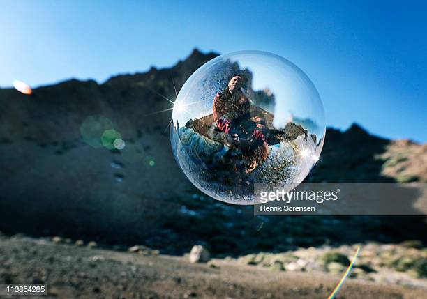 Large soap bubble in mountainous landscape