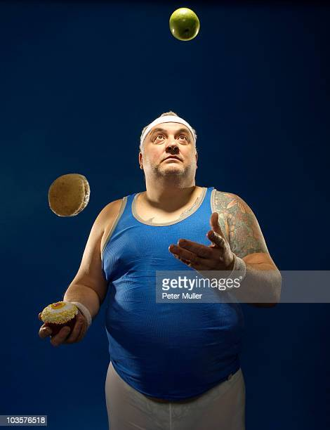 Large sportsman juggling food