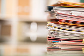 Large stack of files, documents, paperwork on desk.