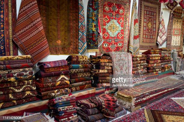 large stacks of oriental persian rugs in a store - persian rug stock pictures, royalty-free photos & images