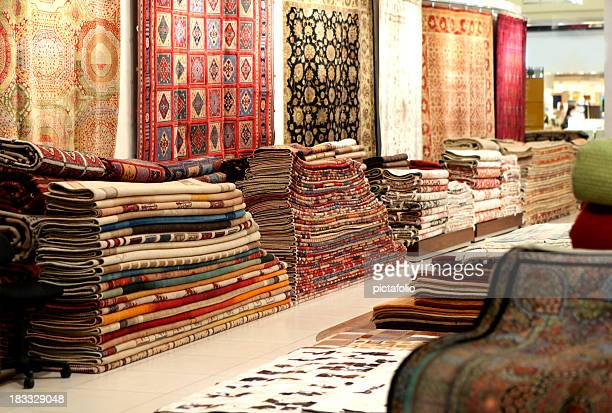Large stacks of oriental Persian rugs in a store