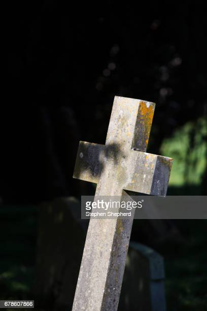 A large stone cross in a church graveyard.