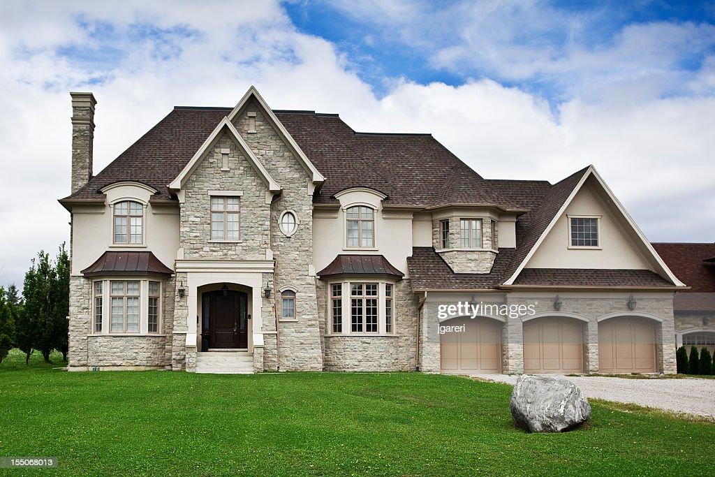 Large stone home with green lawn under blue sky : Stock Photo