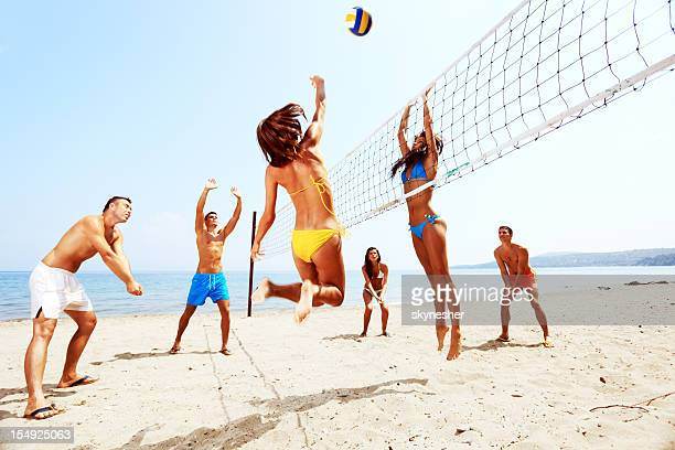 Large team of a people  are playing beach volleyball