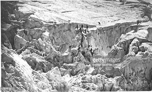 A large team of mountain climbers ascend to a glacial plain on their way to the summit of MontBlanc France 1860
