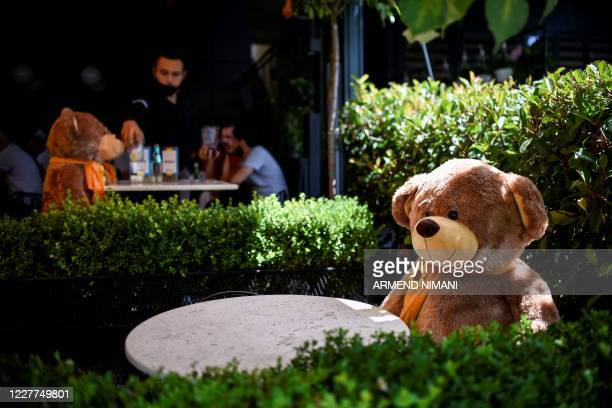 Large teddy bear, used to enforce social distancing, is pictured sitting at a cafe in Pristina on July 23 as Kosovo authorities announce new measures...