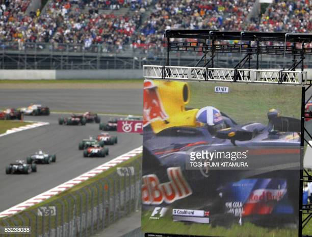 A large television video screen shows the crash of the Great Britain's David Coulthard in his Red Bull after the start of Formula One's Japanese...