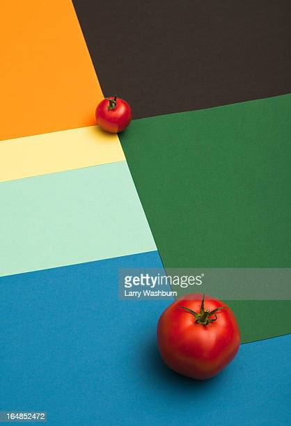 A large tomato and a small tomato placed on a multi colored geometric pattern