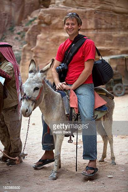 large tourist riding a very small mule - esel stock-fotos und bilder