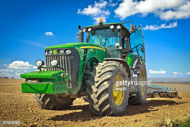 large tractor plowing field - john deere stock pictures, royalty-free photos & images