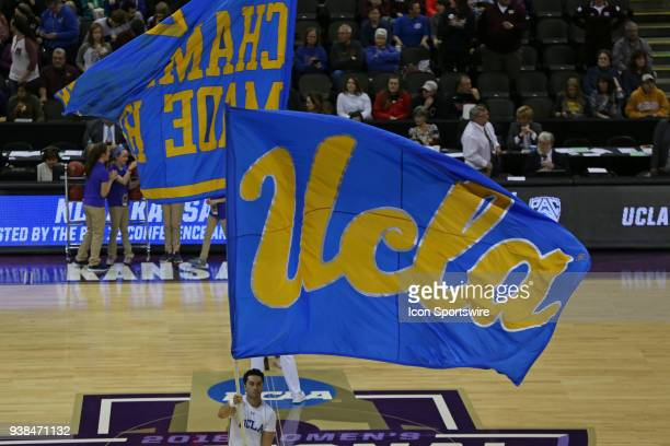Large UCLA flag is carried by cheerleaders before a quarterfinal game in the NCAA Division l Women's Championship between the UCLA Bruins and...