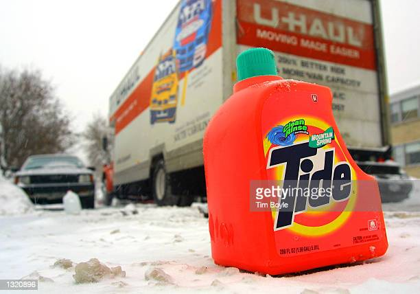 A large UHaul truck threads through a Chicago street December 20 2000 as an empty plastic bottle of Tide laundry detergent protects a resident''s...