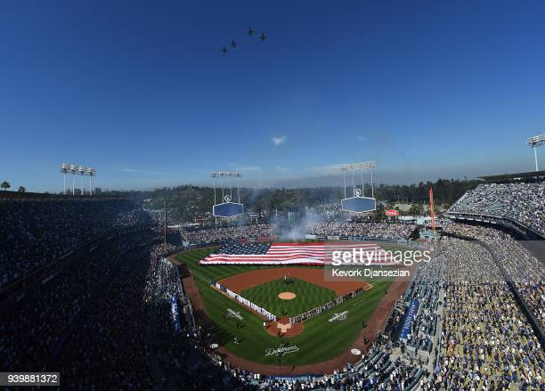 A large United States flag is held up by members of the United States armed forces in the outfield as four T38 Talon planes from Vance Air Force Base...