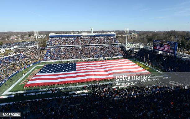 A large US flag covers the field for the national anthem as Navy plays host to Virginia in the Military Bowl at NavyMarine Corps Memorial Stadium in...