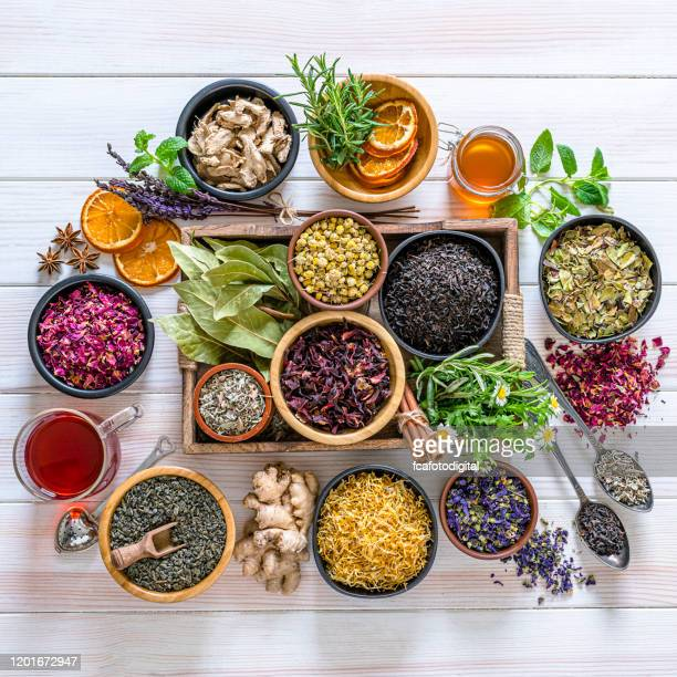 large variety of multi colored dried tea leaves and flowers shot from above on white table - spice stock pictures, royalty-free photos & images