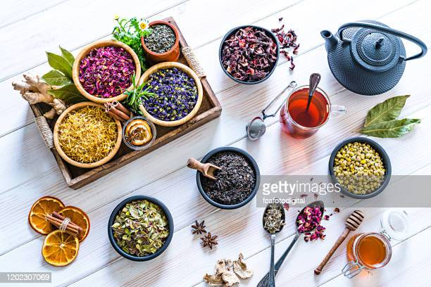 large variety of multi colored dried tea leaves and flowers shot on white table - herbal tea stock pictures, royalty-free photos & images